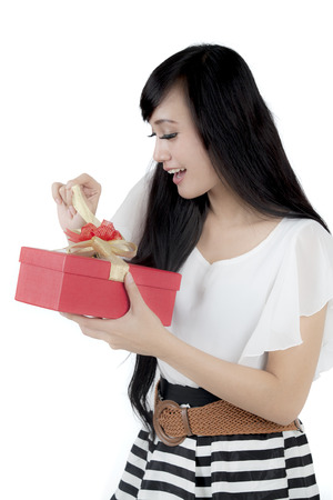 astonish: Pretty businesswoman looks happy while opening a Christmas gift in the studio, isolated on white background