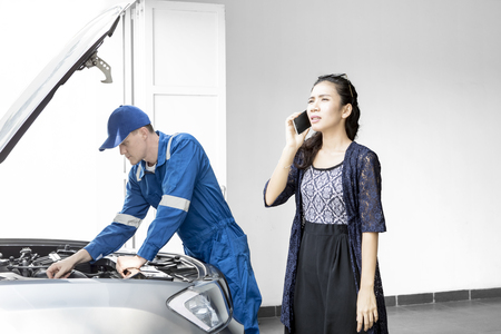 Young woman having problem with her car while speaking on a smartphone and standing with her mechanic