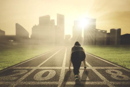 Achtermening van jonge vrouw klaar om naar een stad te lopen terwijl het knielen op de weg met nummer 2018