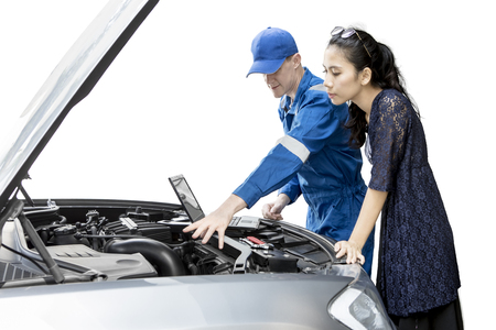 Young male mechanic checking broken car with a laptop while standing with his client, isolated on white background Banque d'images