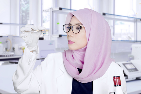 Female Muslim scientist working in the lab and holding a small bottle of chemical experiment sample