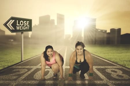 Two obesity women ready to run while kneeling on the road with numbers 2018