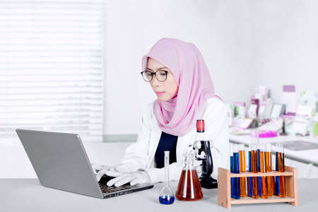Female Muslim scientist working with a laptop computer and test tube in the laboratory