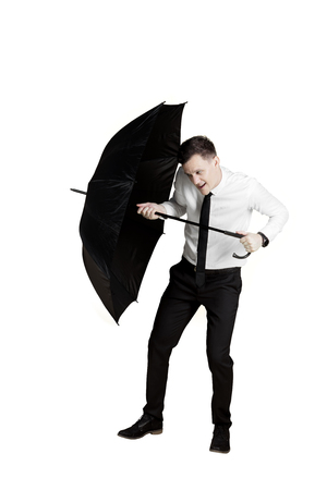 European businessman holds an umbrella for protects himself from trouble, isolated on white background
