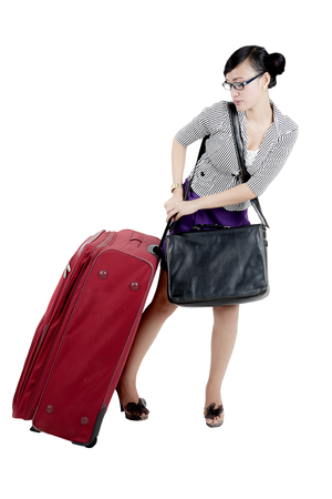 Portrait of female entrepreneur pulling a heavy suitcase while walking on the studio
