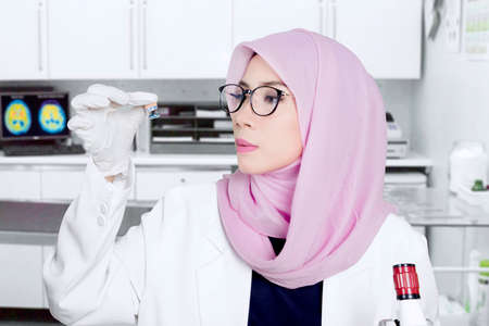 Photo of a young Muslim scientist holds chemical experiment sample with a small bottle in the lab Banque d'images