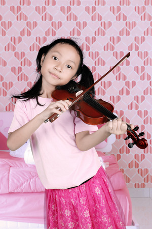 Portrait of little girl playing a music by using a violin while standing in the bedroom Banque d'images