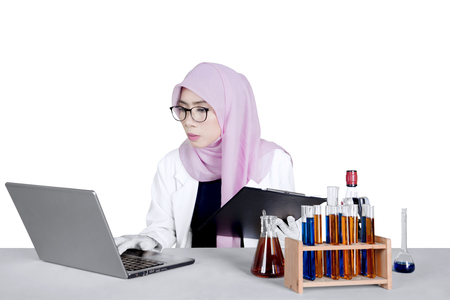 Young Asian chemist working with a laptop, clipboard, and test tube on the table, isolated on white background