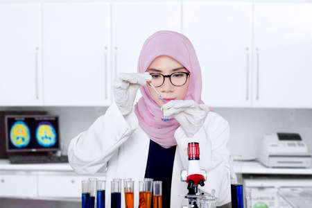 Female Muslim scientist making a chemical experiment using test tube, pipette, and microscope Banque d'images