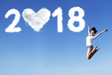 Beautiful woman looks happy while jumping with clouds shaped numbers 2018 and heart in the sky
