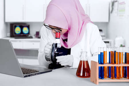 Female Muslim researcher with a laptop computer and test tube on the table, looking through a microscope in the lab