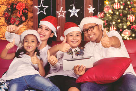 Asian family celebrating Christmas night while showing thumbs up and using a digital tablet at home