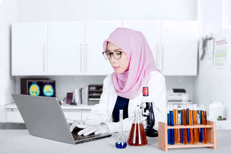 Female Muslim researcher working with a laptop computer, test tube, and microscope in the lab