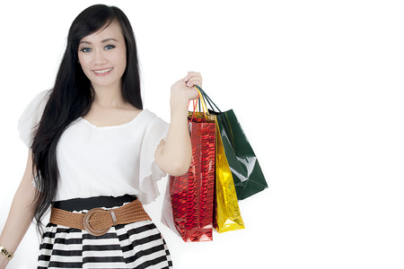 Picture of beautiful woman smiling at the camera while holding shopping bags in the studio