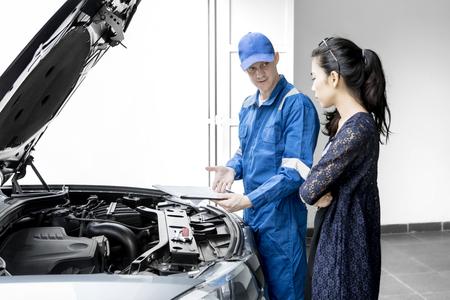 Jonge monteur die een kosten van reparatieservice op het klembord geven aan zijn klant terwijl hij in de buurt van een kapotte auto staat. Ontsproten in de garage
