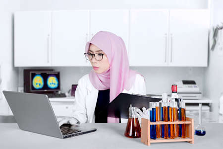 Female Muslim chemist working on the table with laptop computer, test tube and holding a clipboard