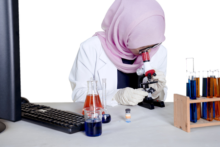 Female Muslim researcher looking through a microscope with test tube and computer on the table