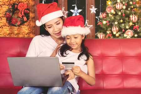 Image of cute little girl and her mother holding a credit card while shopping online at Christmas time