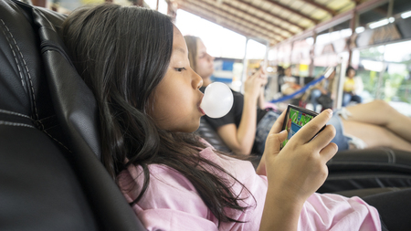 Singapore. November 01, 2017: Cute little girl with bubble gum, playing game on smartphone while sitting in the airport terminal
