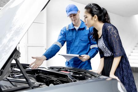 차고에서 정비사와 서있는 동안 그녀의 깨진 된 자동차 기계를 찾고 젊은 여자 스톡 콘텐츠