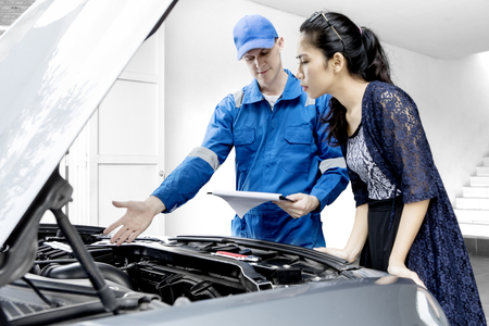 Młoda kobieta, patrząc na jej zepsuty samochód, stojąc z mechanikiem w garażu Zdjęcie Seryjne