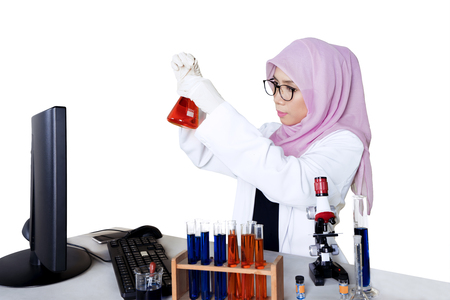 Portrait of a female scientist doing chemical research and using test tube with computer and microscope on the table