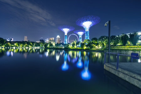 Singapore. November 06, 2017: Beautiful view of Gardens by the Bay with Supertrees Grove and Singapore Flyer reflection on the water at night