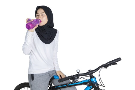 Portrait of a young muslim woman riding a bike while drinking a bottle of fresh water, isolated on white background