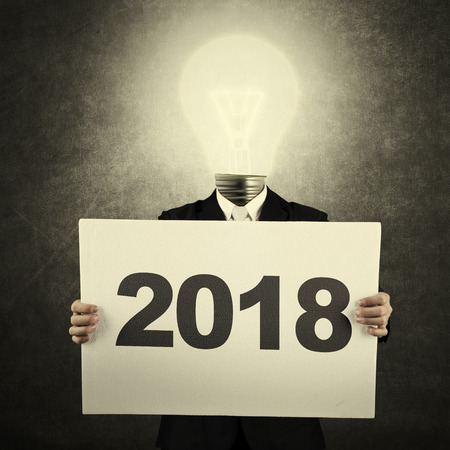 Image of businessman with light bulb head while holding numbers 2018 on the billboard