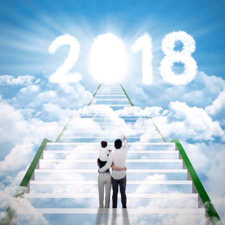 Young family walking on the stair toward to clouds shaped number 2018 with shining door