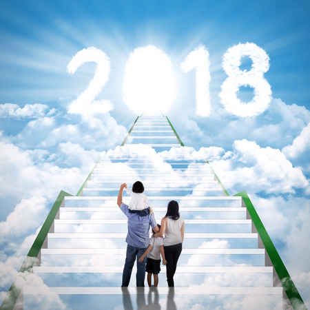 Back view of young family standing on the stairway while looking at clouds shaped number 2018 with shining door