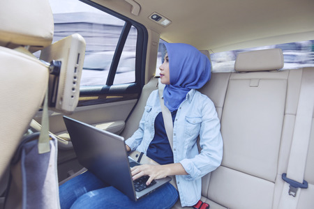 Photo of a young female muslim using a laptop computer inside a car while looking out through the window Banque d'images