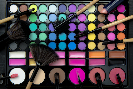 Top view of various professional makeup tools with eyeshadow palette