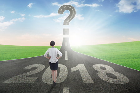 Back view of businesswoman standing above numbers 2018 while looking at a question mark on the end road Stock Photo