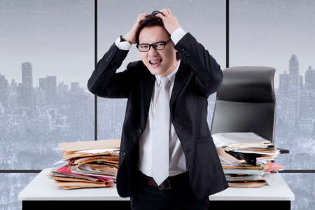 Image of Asian male manager having a headache while overworking in the office