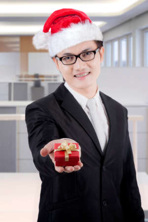 Young businessman smiling at the camera while offering a Christmas gift. Shot in the office Banque d'images
