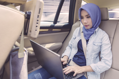 Portrait of a young muslim woman with a laptop computer in the car