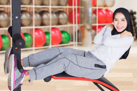 Photo of a female muslim doing crunches workout in the fitness center