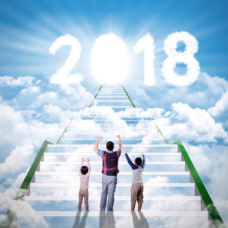 Achtermening van jonge vader met zijn kinderen die wolken gestalte gegeven nummer 2018 met glanzende deur bekijken