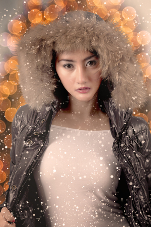 Beautiful female model wearing winter jacket while standing under snowfall with lights blur in the background Banque d'images