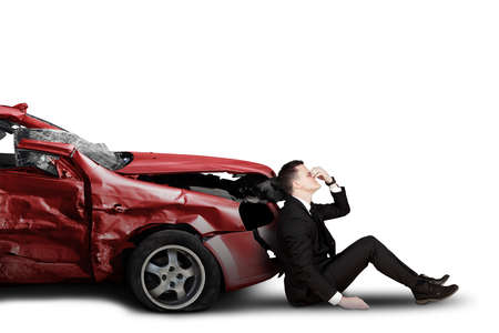 Stressful Caucasian businessman sitting near a damaged car, isolated on white background Banque d'images