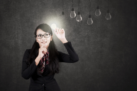 Image of Asian businesswoman thinking a solution while holding a light bulb