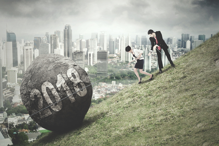 Business people climbing on the hill while pulling a rock with numbers 2018 and a city background
