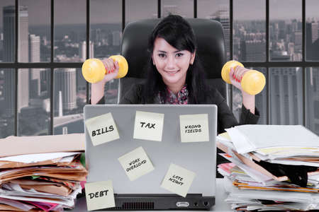 Image of young businesswoman exercising with dumbbells while working with a laptop and piles of paperwork