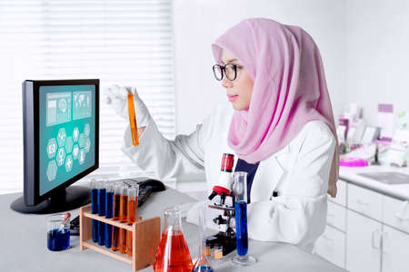 Female muslim working in the lab while holding a test tube with microscope and computer on the table