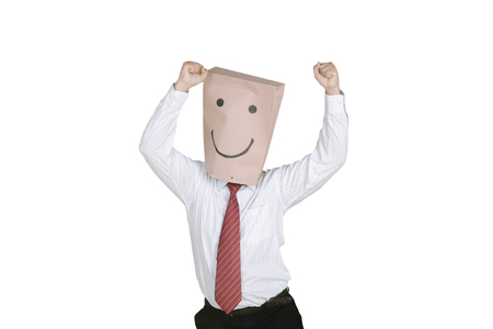 Successful unknown businessman celebrating his success while raising hands with a paper bag on his head
