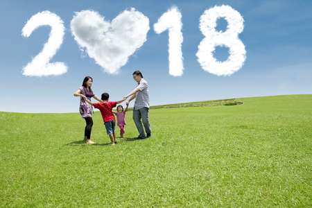 Happy family having fun together in the meadow with clouds shaped numbers 2018 and heart in the sky Stock Photo - 90661572