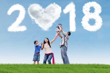 Young parents playing with their children in the meadow with clouds shaped numbers 2018 and heart Stockfoto