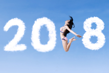 Happy woman wearing swimsuit while flying with clouds shaped numbers 2018 in the blue sky Stock Photo