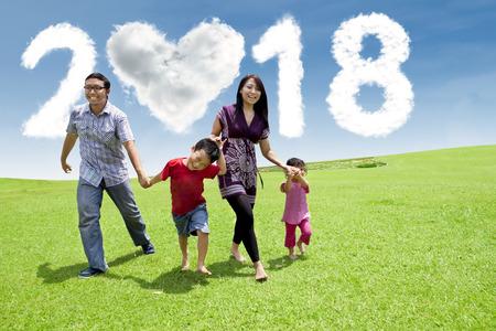 La famiglia asiatica che ride insieme mentre cammina nel parco con le nuvole ha modellato il cuore ed i numeri 2018 nel cielo Archivio Fotografico - 90677898